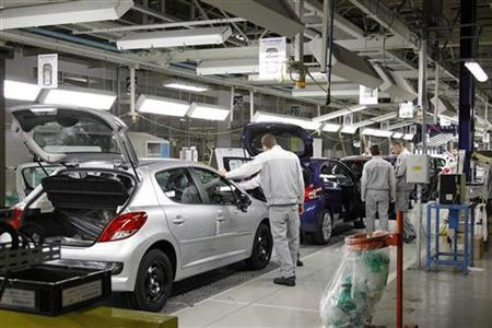 Employees work on the assembly line of the Peugeot 207 and Peugeot 208 at the PSA Peugeot Citroen plant in Poissy